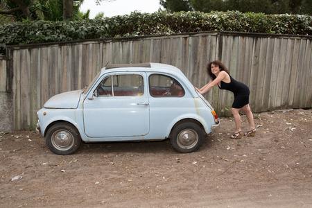 break down: Woman is pushing a small blue car break down Stock Photo