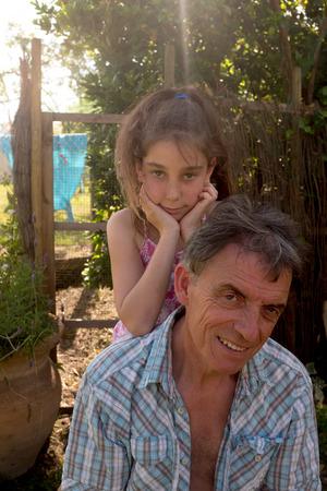 grandchild: Outdoor lifestyle portrait of grandchild embracing grandfather
