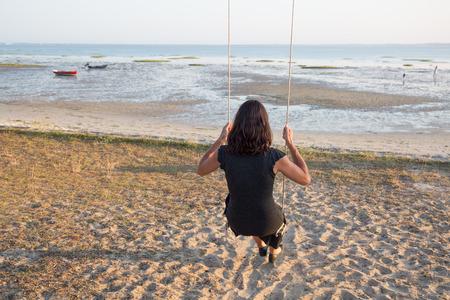 mujer mirando el horizonte: Volver la vista de una mujer en un columpio en un océano playa viendo Foto de archivo