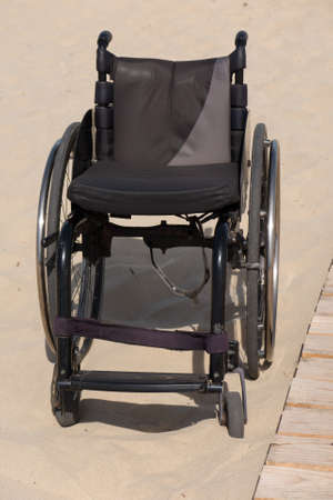 vacant: Empty wheelchair sits vacant on a beach of sand Stock Photo