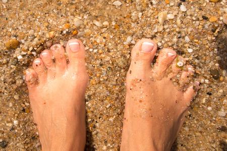 sandy feet: Female feet relaxing on the sandy beach Stock Photo