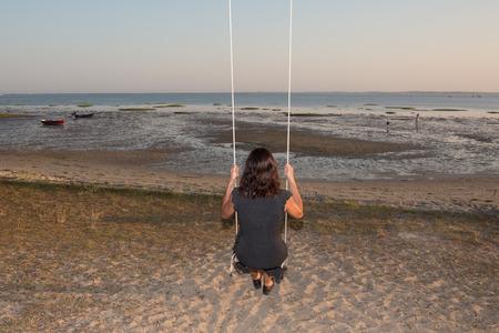 mujer mirando el horizonte: Volver la vista de una mujer en un columpio en un oc�ano playa viendo Foto de archivo