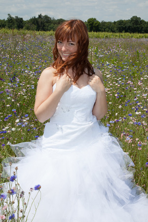 carelessness: Young bride walking on the flower meadow