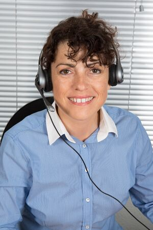 entrepeneur: Smiling and happy woman with headphone at office