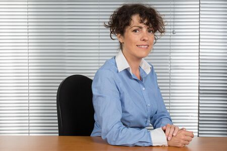 buisness woman: smiling caucasian businesswoman sitting in office looking at the camera Stock Photo