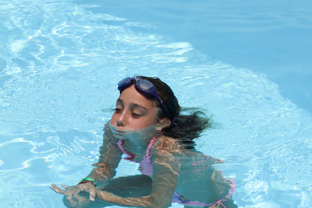 10 years old: Girl 10 years old with googles in swimming pool