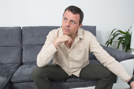 classy house: Portrait of a  relaxed man sitting on sofa in the house
