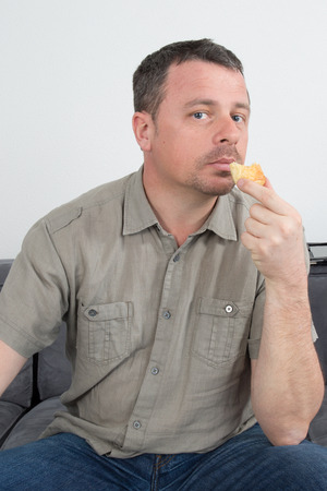 kanapa: Man on his couch eating something