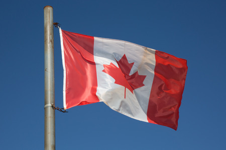 canadian flag: Canadian flag waving in the air over a beautiful blue sky Stock Photo