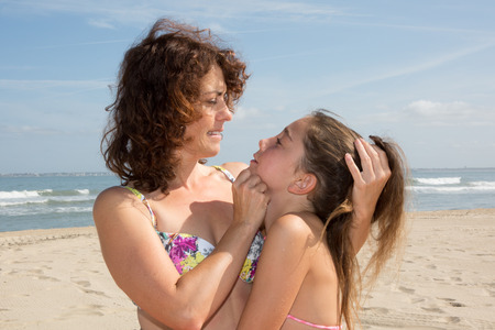 adorable child: Love  between a mother and her daughter at the beach