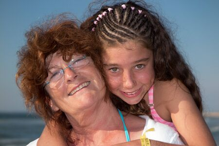 grand daughter: Grand Mother Giving daughter ride on Back at the beach