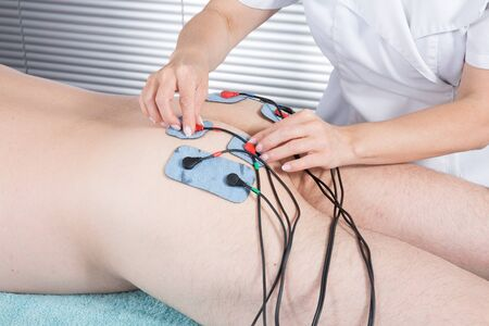 stimulator: Man getting electric massage for leg muscles in spa