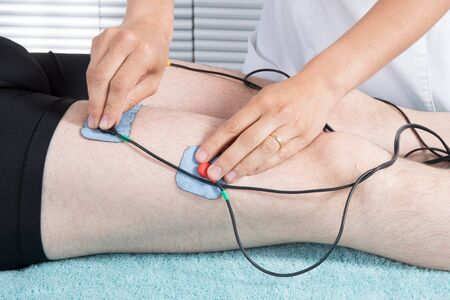 the weakening: Man getting electric massage for leg muscles in spa
