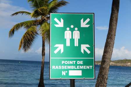 assembly point: Evacuation assembly point sign under blue sky and paradise seascape