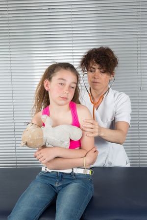 healing practitioners: Happy little girl at the doctor for a checkup - being examined with a stethoscope Stock Photo