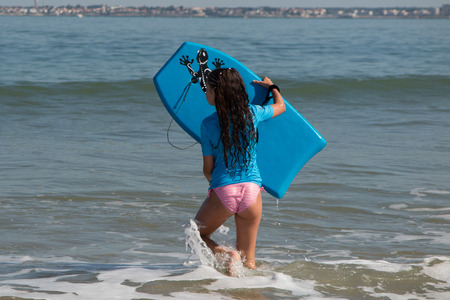 Happy young girl surfing during holidays Stock Photo