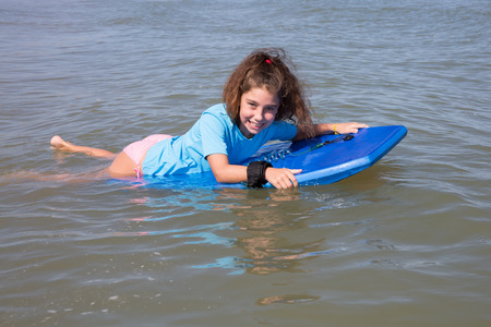 Young girl surfing with her board