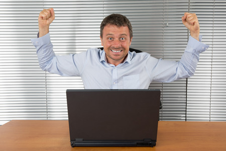winner man: Excited businessman shouting of joy and gesturing with raised clenched fists over successful business deal in front of a computer over dark grey background. Stock Photo
