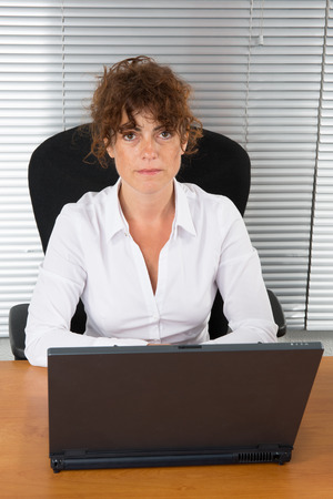 busineswoman: Happy busineswoman sitting in the office with laptop