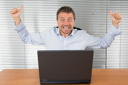 deal in: Excited businessman shouting of joy and gesturing with raised clenched fists over successful business deal in front of a computer over dark grey background. Stock Photo