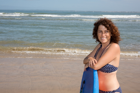 woman middle age: Woman middle age with a body board on the beach Stock Photo