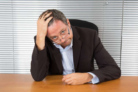 too much work: Too Much Work. Portrait of exhausted businessman sitting at office desk Stock Photo