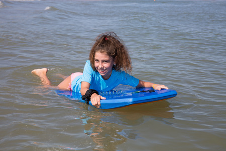 bodyboarding: Pretty girl on the beach surfing on the body board