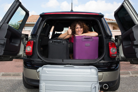 go for: Suitcases and bags in trunk of car and woman ready to go for holidays