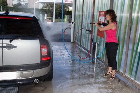 water jet: Woman washing his car with a high pressure water jet