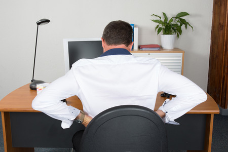 back ache: businessman suffering from back ache in front of laptop in the office