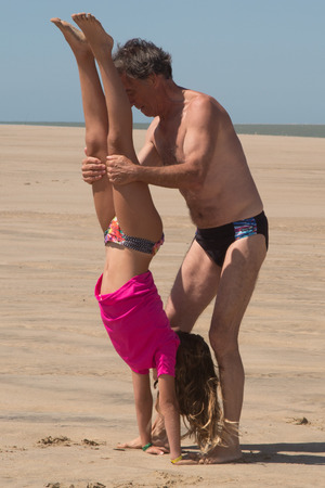 grand daughter: Father and daughter playing on the beach at  Concept of friendly family.
