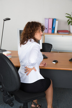 back ache: Business woman suffering from back ache in front of laptop in the office