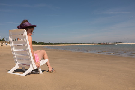 Girl sitting in chaise longue on the beach