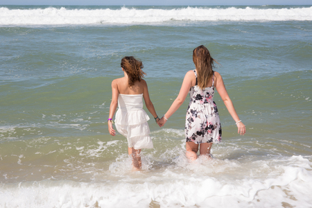 semi dress: Girls at the sea. Two young women come into sea, rear view