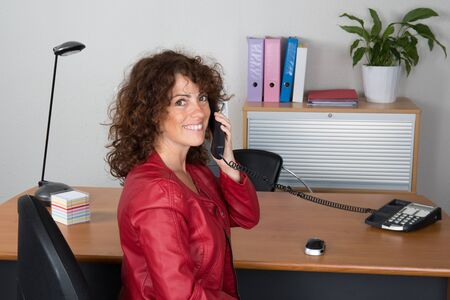 buisness woman: Business girl with a red leather jacket on a phone