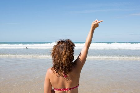 copysapce: An image of a girl pointing her finger  in front of the ocean - copyspace