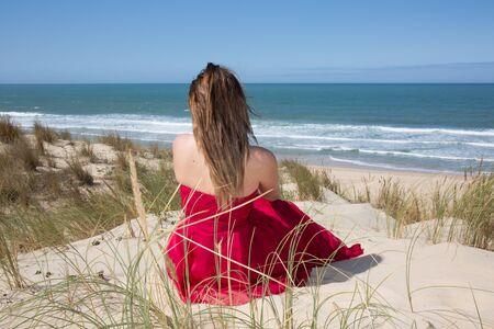 admiring: female with a red dress admiring a marine view Stock Photo