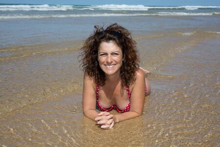 Portrait of smiling middle age woman laying on beach
