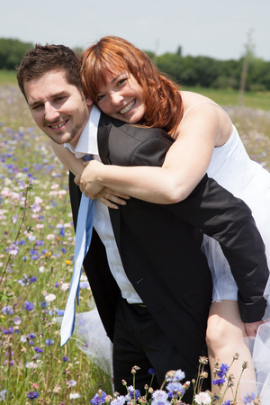 newly wedded couple: Newly lovely wedding couple happy in the country piggy back Stock Photo
