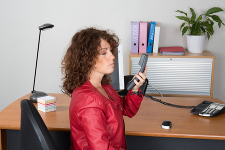 buisness woman: Business girl with a red leather jacket at work