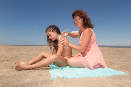 putting on: Mother And Daughter Putting On Sun Cream