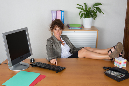 winning business woman: Relaxed and winning business woman sitting with her legs on desk