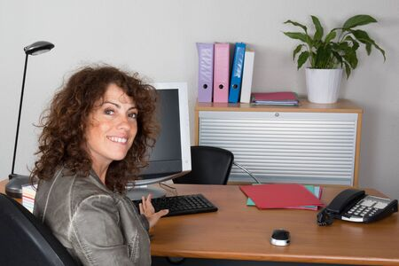 at her desk: Brunette  female at her desk at office Stock Photo