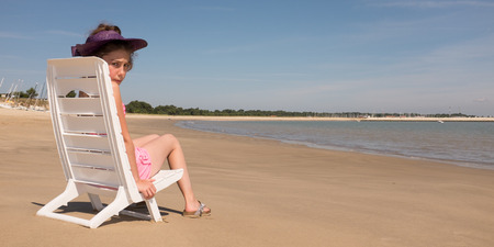 longue: Girl sitting in chaise longue on the beach