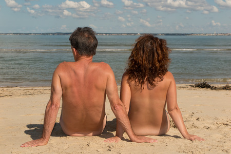 nude yoga: Naked couple sitting on the beach.