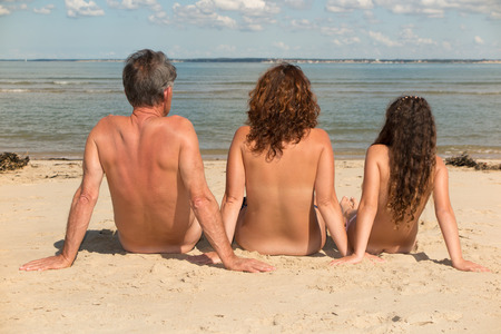 Naked family sitting on the beach. Stock Photo