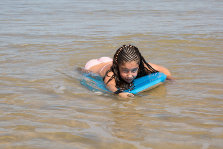 bodyboard: Lovely girl smiling at the camera on her bodyboard Stock Photo