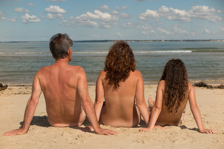 nude yoga: Naked family sitting on the beach. Stock Photo