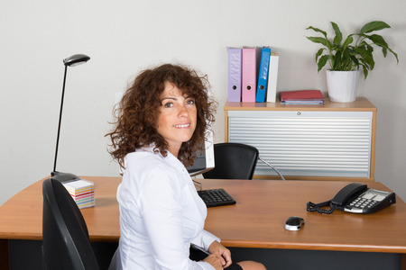 Woman at work with a white shirt happy to work