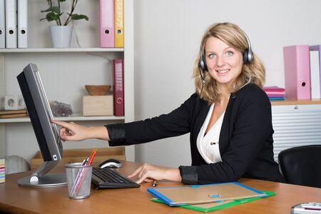 call center agent: Fiducioso agente di call center bionda che lavora al computer in ufficio luminoso